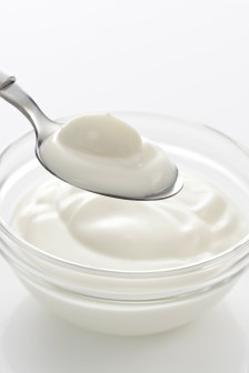 Bowl and spoon with yogurt on white background, close up